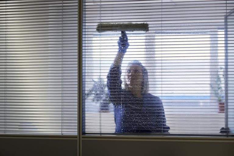 mujer ñimpiando el cristal de su oficina