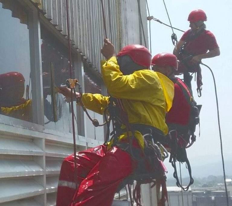 personas limpiando el cristal de un edificio con cascos rojos
