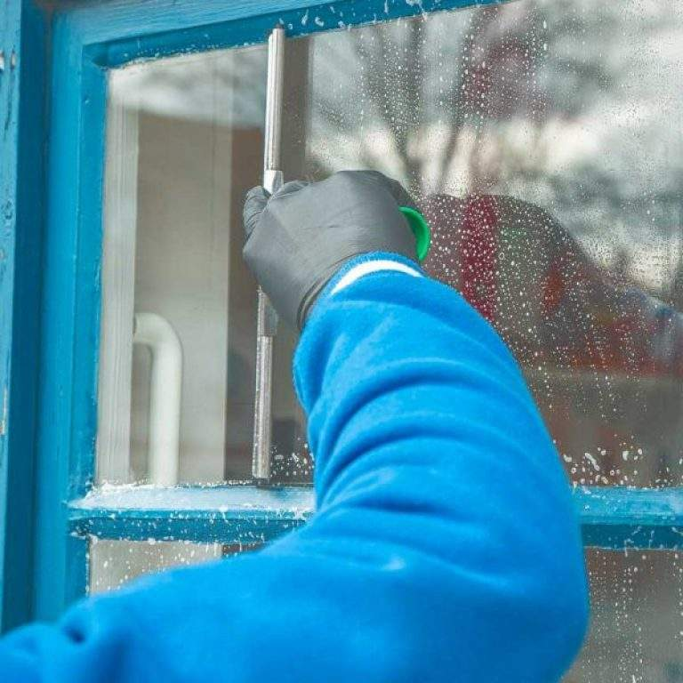 persona limpiando cristales con guantes negros