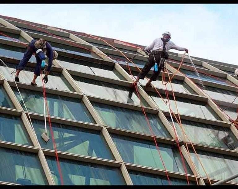 dos personas limpiando las ventanas de una edificación